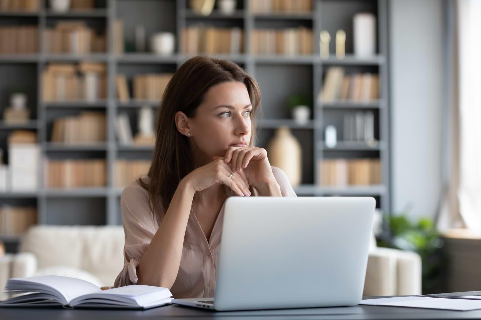 Kvinna vid dator funderar över att låna till investering