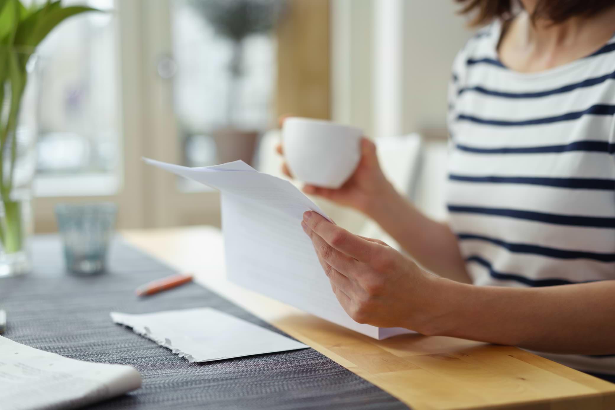 Kvinna vid ett bord som läser en kreditupplysningskopia