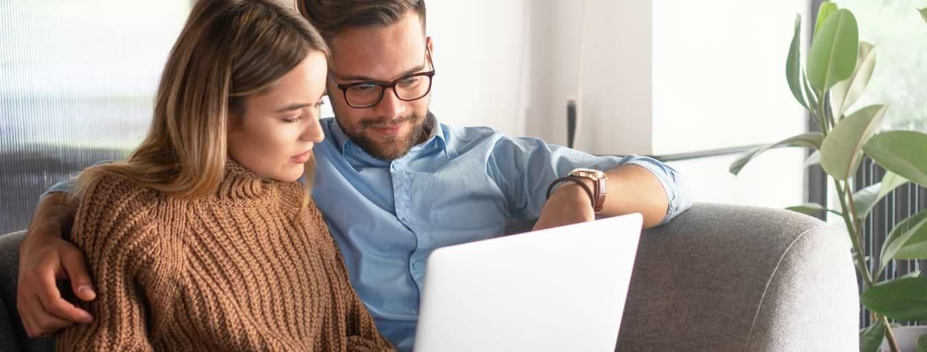 Man och kvinna i en soffa som ansöker om lån på datorn