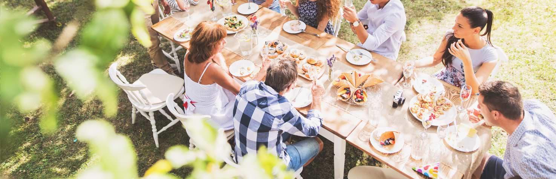 Familj som äter vid ett bord utomhus på sommaren