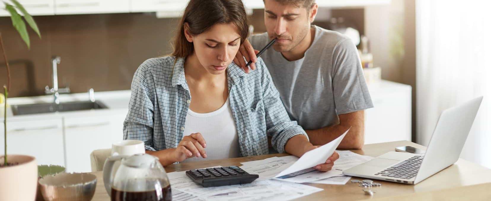 Man och kvinna med kalkylator som räknar på lån