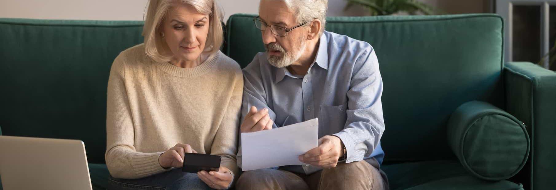 Ett äldre par som går igenom räkningar vid dator