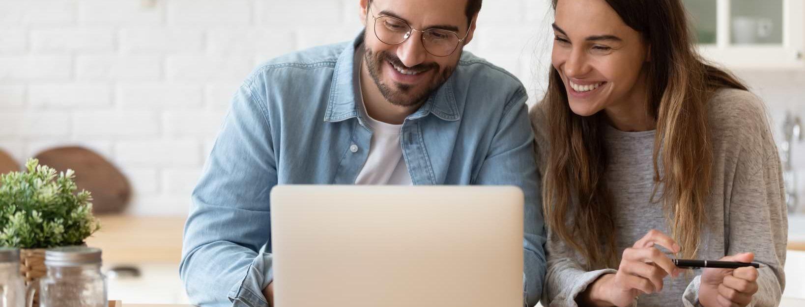 Man och kvinna vid dator som budgeterar
