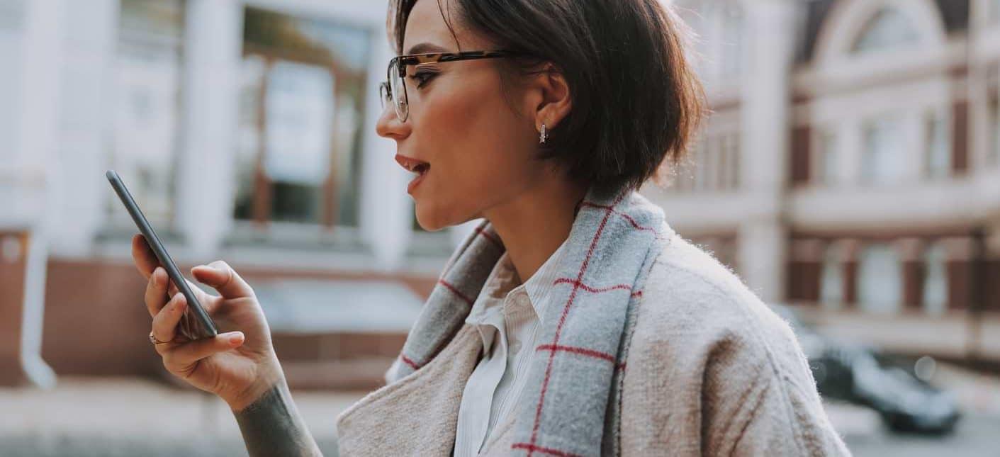 Kvinna som kollar sitt kreditbetyg i mobilen