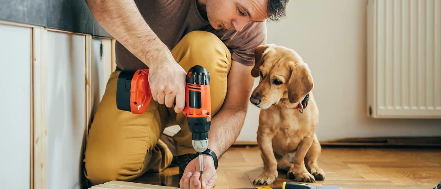Man som borrar i en planka med hund bredvid