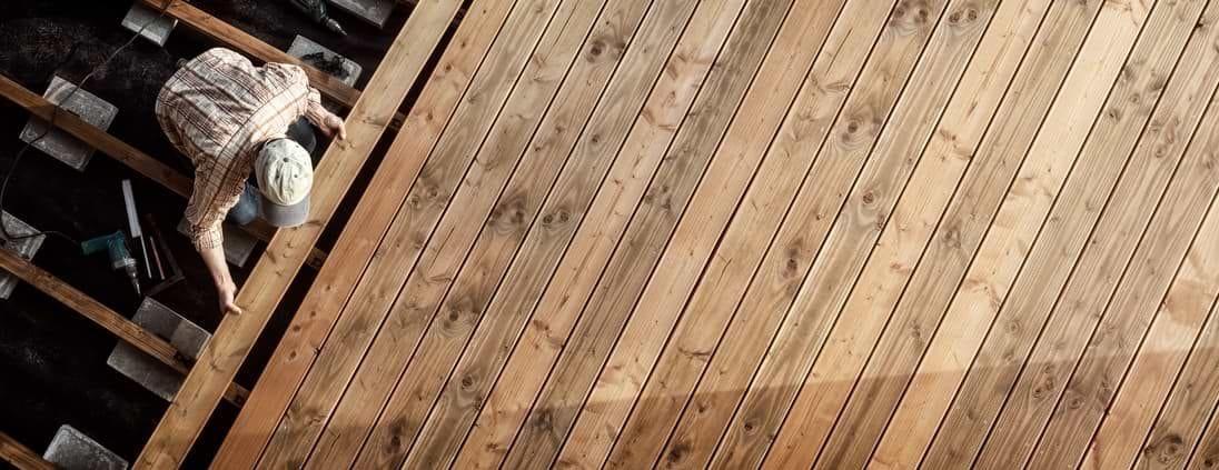 Man uppifrån som bygger trädäck