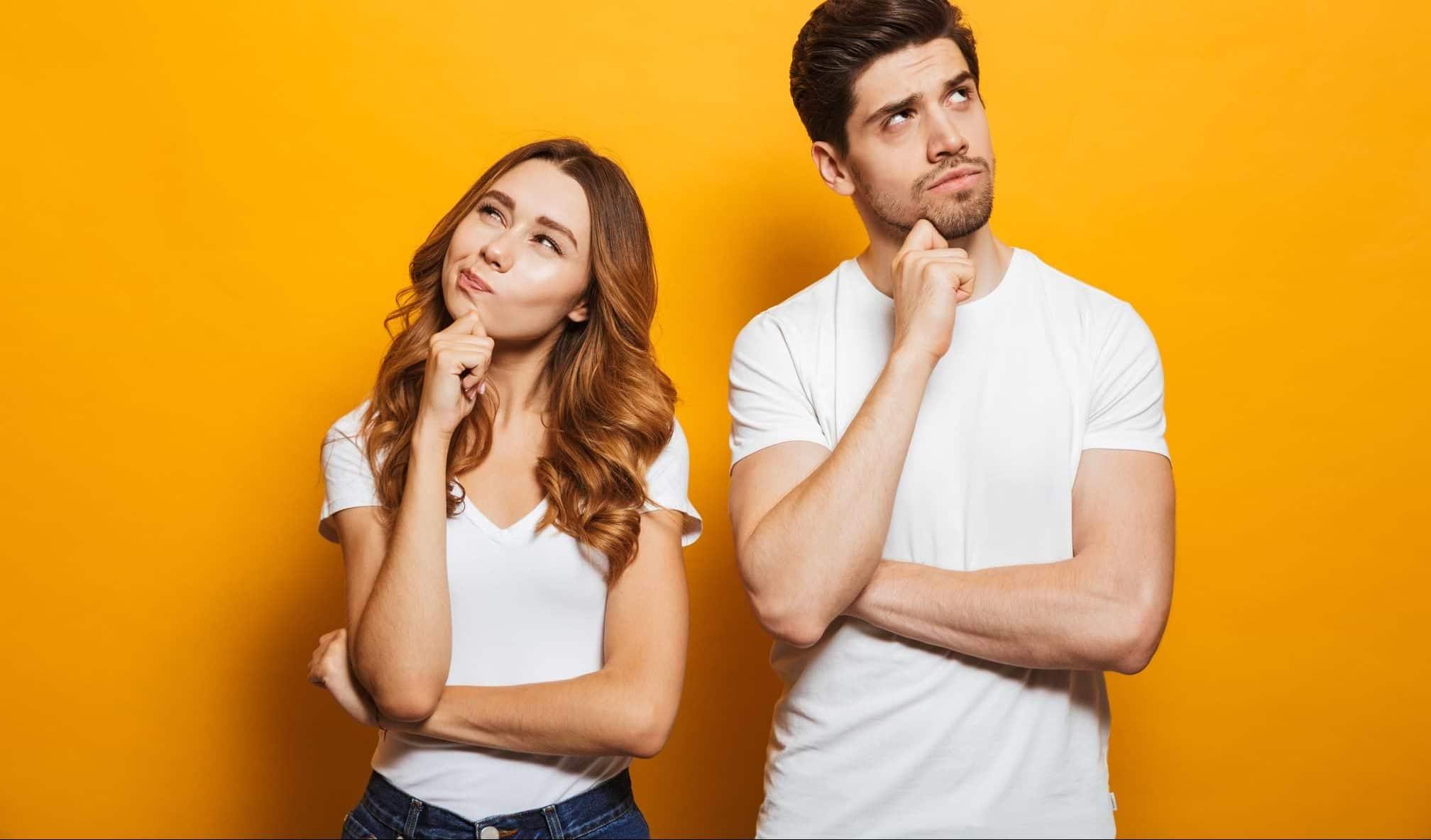 Fundersam man och kvinna mot orange bakgrund