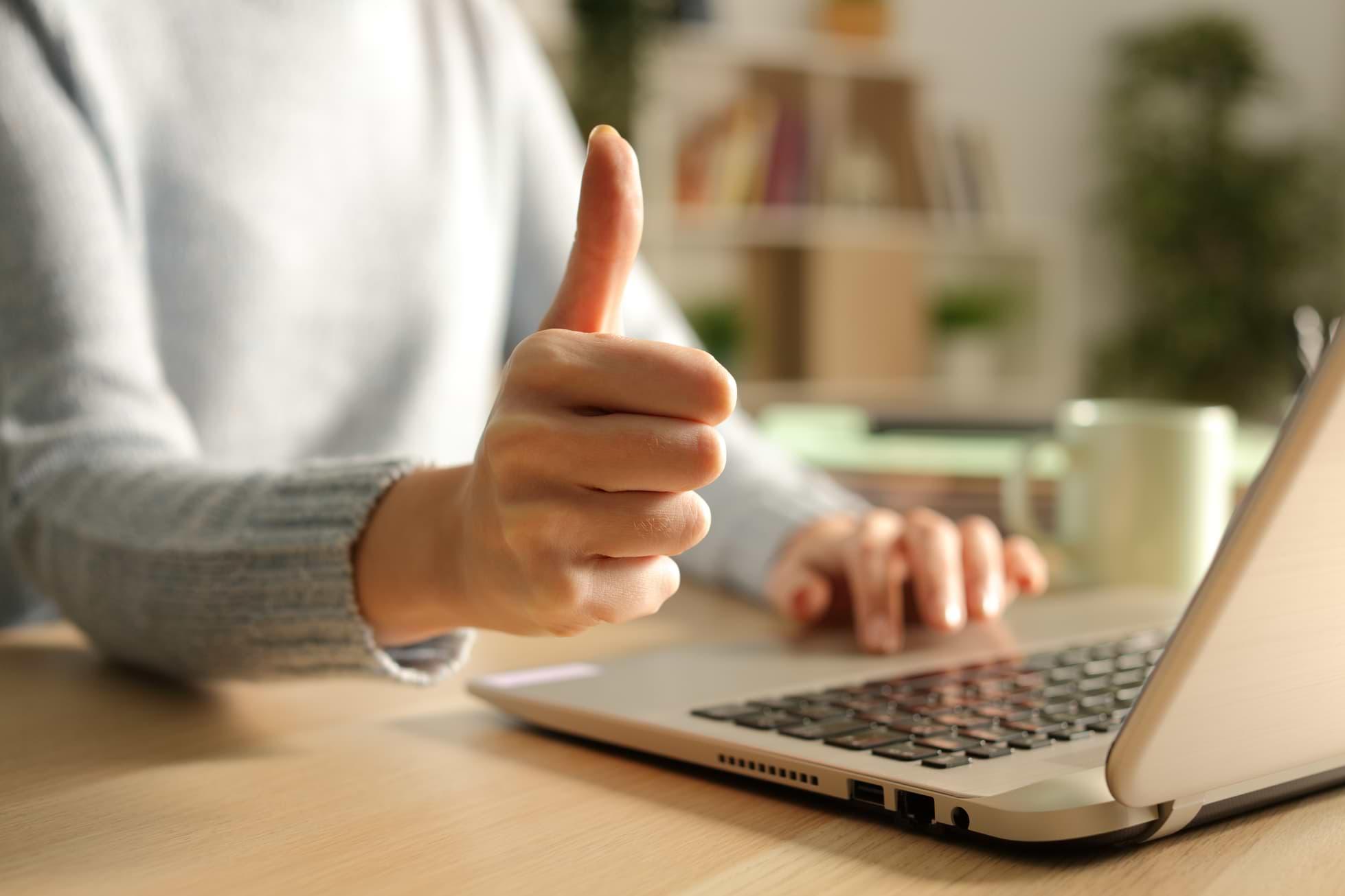 Kvinna vid dator gör tummen upp
