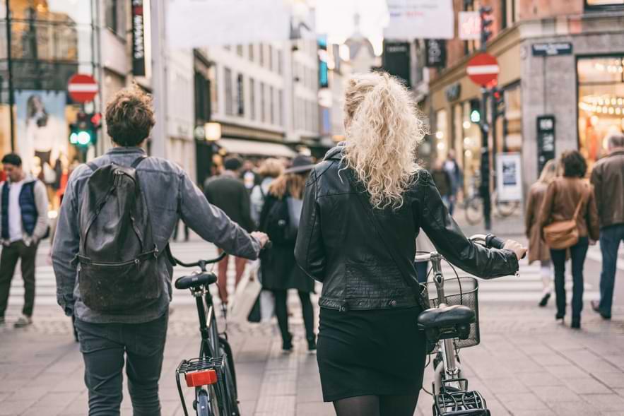 Man och kvinna leder cyklar på gågata
