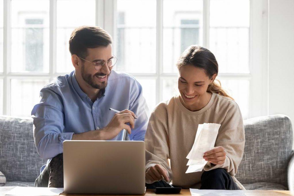 Par vid dator som gör hushållsbudget