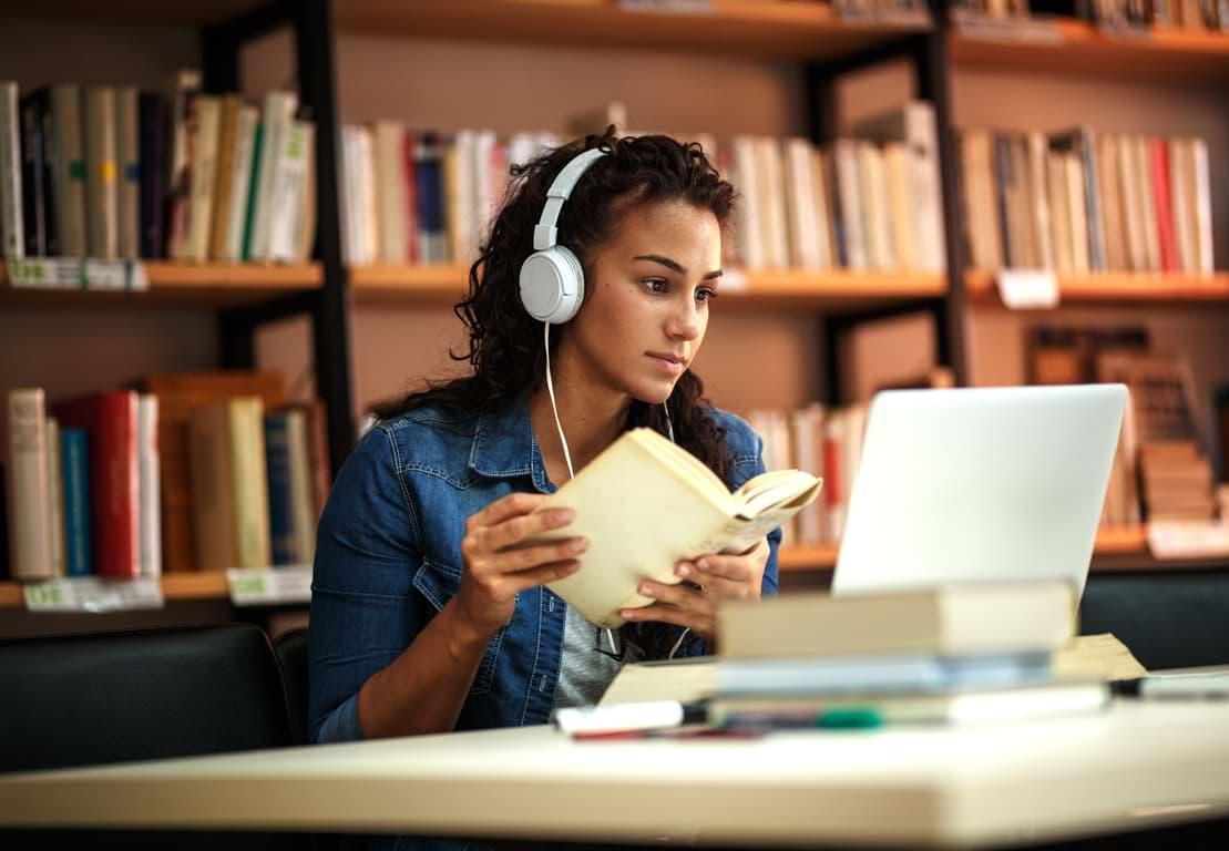 Studerande kvinna i bibliotek