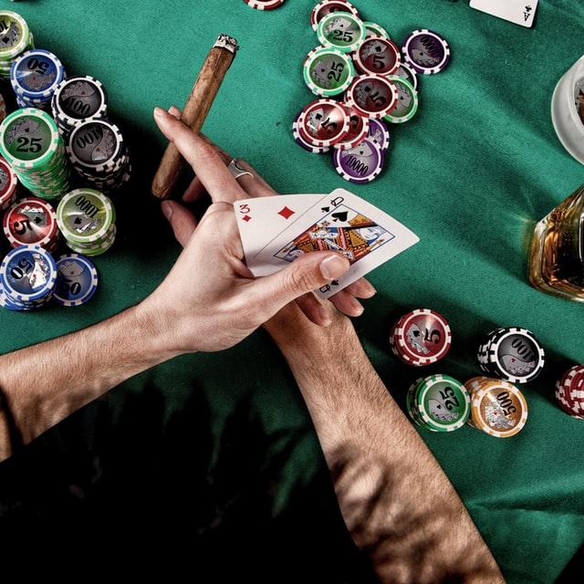 Ett par händer som håller i spelkort och en cigarr över ett bord med spelmarker och ett glas sprit.